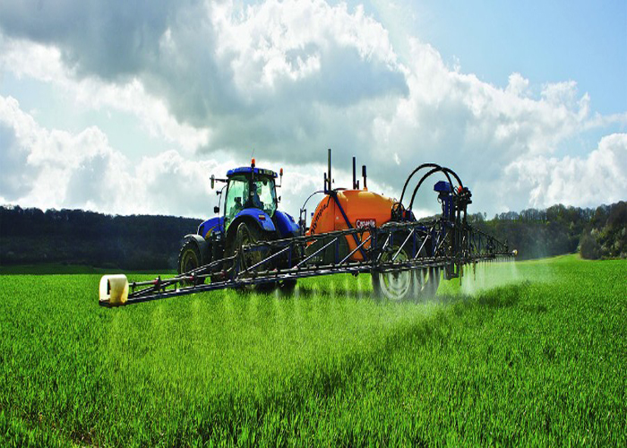A tractor spraying chemicals on crop.